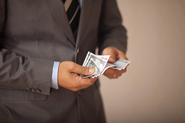 En man hanterar en summa pengar.